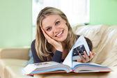 Muito jovem mulher deitada no sofá lendo um livro — Foto Stock