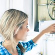 Stock Photo: Beautiful Girl Is Seting Up Boiler