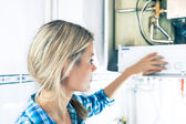 Beautiful Girl Is Seting Up a Boiler — Stock Photo