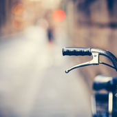 Handlebar of an Old Bike Resting in the Narow Street (vintage co — Stock Photo