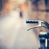 Manillar de una vieja bicicleta descansando en la calle narow (vintage co — Foto de Stock