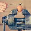 Detail of Hand with Spoon Tapping an Egg Fixed in Vice — Stock Photo