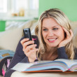 Young Woman Sending SMS with Mobile Phone While Lying at Home on — Stock Photo