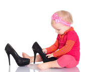 Cute little baby girl trying on her mother's shoes on white back — Stockfoto