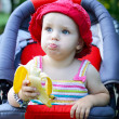 Baby sitting in a pram eating banana — Foto Stock