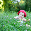 Cute little girl sitting in the green field — Foto de Stock