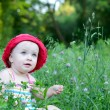 Cute little girl sitting in the green field — Foto Stock