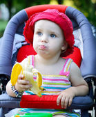 Baby sitting in a pram eating banana — Stock Photo