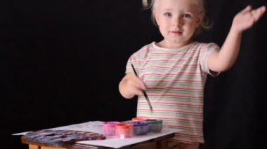 Cute little baby painter on black background. — Vidéo