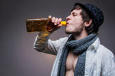 Fashionable guy in a hat drinking tequila — Stock Photo