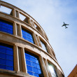 Jet over curvy building — Stock Photo #14955477