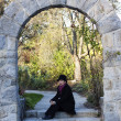 Woman seated on steps of stone archway — Stock Photo