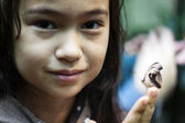 Butterfly on young girl's finger — Stock Photo