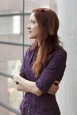 Teacher standing at window smling - gazing upward — Stock Photo