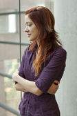 Businesswoman standing at window smling - looking down — Stock Photo