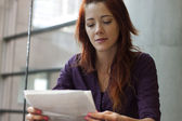 Businesswoman reading over financial documents - smiling — Stock Photo