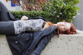 Woman lying on stone flower bed — Stock Photo