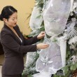 Stock Photo: Pretty asilady trimming crhistmas tree