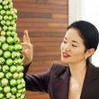 Pretty asian lady placing glittery ball on ornate christmas tree - portrait — Stock Photo