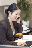 Pretty asian businesswoman at computer on phone — Stock Photo