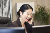 Pretty asian businesswoman smiling on phone — Стоковое фото