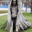 Creepy tree sculpture of hooded figure — Stock Photo