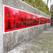 Red strip posting on cement wall — Stock Photo