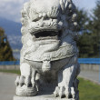 Stone lion by waterfront - Stock Photo
