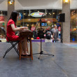 Chinese girl playing zither in mall - Stock Photo