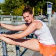 Stock Photo: Hamstring stretch on railing