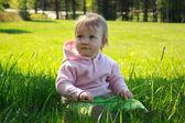 Malá dívka sedící v trávě — Stock fotografie