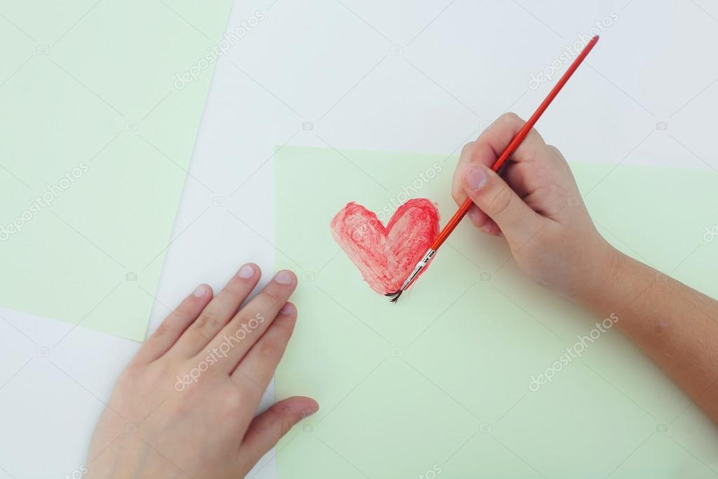 Girl hands painting a red heart — Stock Photo #18458589