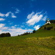 White clouds in blue sky and a little church in mountain — Stock Photo #16622061