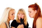 Three beautiful girls sing into the microphone — Stock Photo