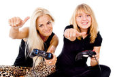 Two happy girls play video games — ストック写真