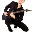 The handsome young man sits and plays the electric guitar — Stock Photo #15628467
