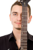 Beautiful guy thinks, pressed to the guitar — Stock Photo