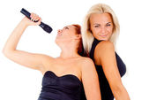Two girl sing into the microphone — Stock Photo
