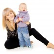 A happy mother sits with her little baby — Stock Photo #16795853