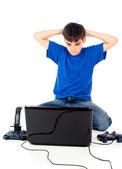 Chico con un ordenador portátil y joystick — Foto de Stock