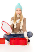 Girl in a hat sitting with gift boxes — Stock Photo