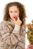 Girl in a sweater eating chocolate candy — Stock Photo