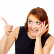 Beautiful red-haired girl points a finger — Stock Photo #17382421