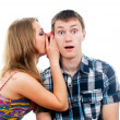 Beautiful girl says a guy whispers in your ear — Stock Photo