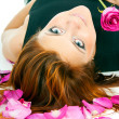 Beautiful redhead girl with rose petals — Stock Photo #17382465