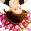 Girl lying on a background of rose petals — Stockfoto