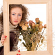 Stock Photo: Girl with a frame and a still life of flowers