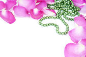 Background with rose petals and heart bead — Stock Photo