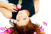 Beautiful girl lying on a background of rose petals — Stok fotoğraf