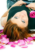 Beautiful redhead girl with rose petals — Stock Photo